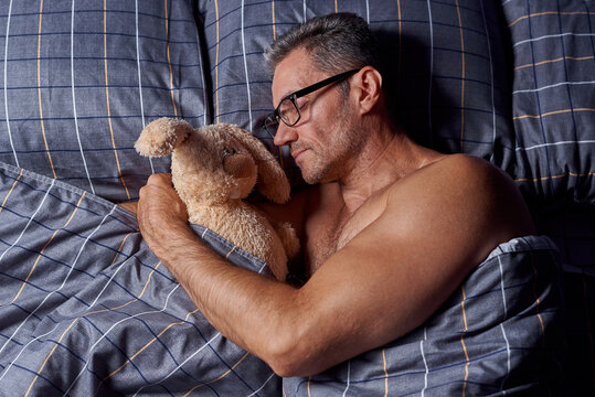 A young man sleeps in an embrace with a stuffed rabbit in bed.