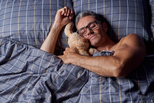 Tired young man sleeping with stuffed rabbit in bed.
