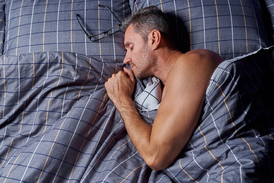 Sleeping young man in bed under the duvet.