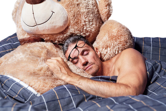 A young man sleeps in an embrace with a teddy bear in bed on a white background.