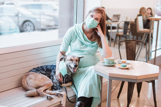 Pregnant women and her dog in medical face mask are sitting at the table in cafe. Pregnancy concept. Pet's care concept.