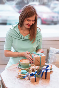 Young smiling pregnant woman in cafe with cup of coffee and Christmas gifts. Pregnant lifestyle.
