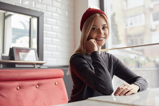 Woman looking and smiling at camera in cafe
