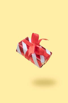 Christmas gift box levitation on warm background. Holiday gift concept.