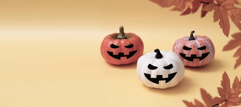 Three pumpkins with smiling halloween faces, autumn baner with copy space
