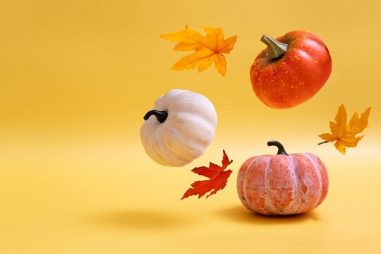 Three pumpkins on warm background. Levitation autumn, halloween concept. Copy space.