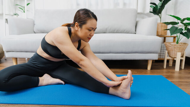 Portrait of gorgeous young asian woman practicing yoga at home stretching out while following a yoga routine