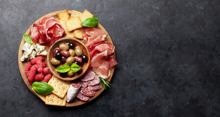 Antipasto board with prosciutto, salami, crackers, cheese, olives