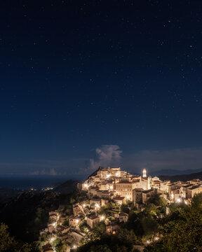 Stars over the illuminated mountain village of Speloncato in the Balagne region of Corsica