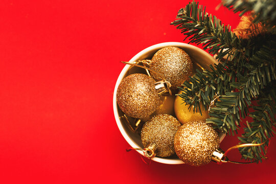 Gold balls and toys in a white cup with a branch of a Christmas tree on a red background