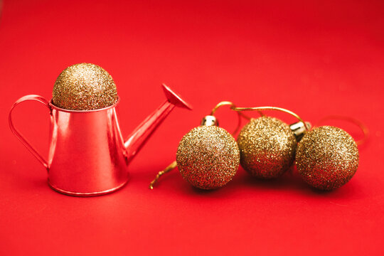Gold balls and decorative watering can on a red background