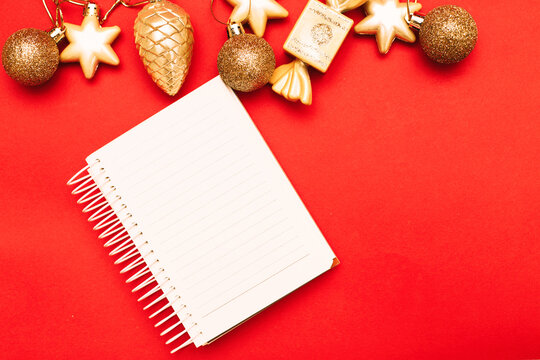 Gold Christmas balls and toys with empty blank note sheet on a red background