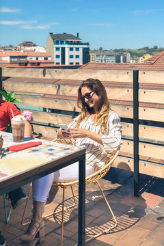 Smiling woman looking cell phone and having a milkshake on a terrace