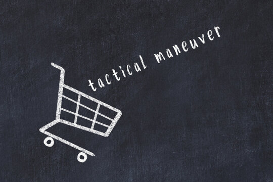 Chalk drawing of shopping cart and word tactical maneuver on black chalboard. Concept of globalization and mass consuming