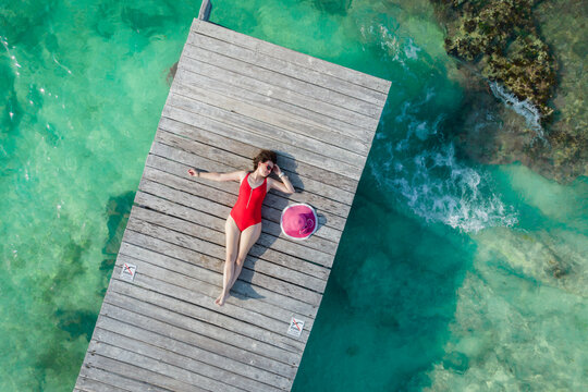 Aerial view of woman on wooden pier at sunny summer day in Cancun, Mexico, top view. Young sexy woman in the red swimsuit in summertime in Caribbean. Summer beach vacation concept