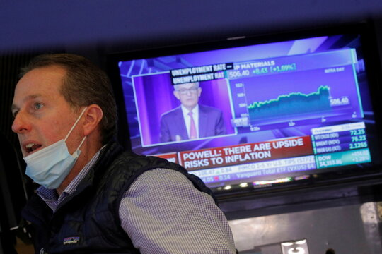 A trader works on the trading floor as a screen displays a statement by Federal Reserve Chair Jerome Powell following the U.S. Federal Reserve's announcement at the NYSE in New York
