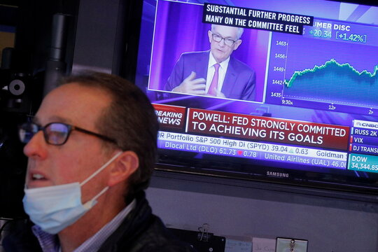 A screen displays a statement by Federal Reserve Chair Jerome Powell following the U.S. Federal Reserve's announcement as a trader works on the trading floor of the NYSE in New York