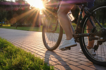 Man rides a bike outdoors in the park on a sunny day at sunset close-up. Active lifestyle