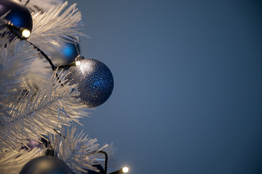 Festive image of blue christmas bubbles on white holiday tree