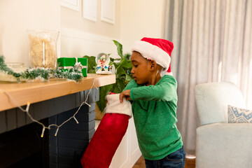 African american boy wearing santa hat and searching for present in christmas stocking