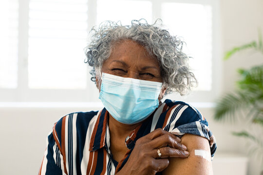 Happy senior african american woman wearing face mask with plaster on arm after vaccination