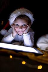 Caucasian boy wearing santa hat, using tablet, looking at camera at christmas time