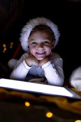 Happy caucasian boy wearing santa hat, using tablet, looking at camera at christmas time