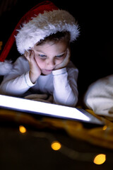 Focused caucasian boy wearing santa hat, using tablet at christmas time
