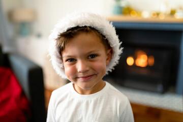 Happy caucasian boy wearing santa hat looking at camera at christmas time