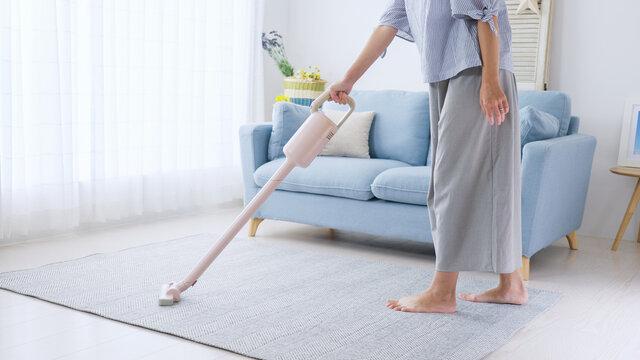 部屋の床に掃除機をかける若い女性・主婦