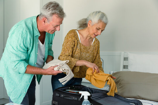 Caucasian senior couple packing suitcase together and talking in bedroom