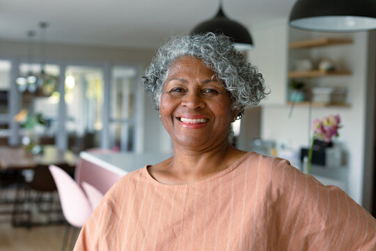 Happy african american senior woman standing standing in kitchen and looking at camera