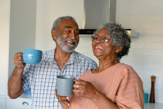 Happy african american senior couple holding mugs with coffee and talking