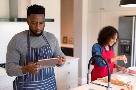 Focused african american couple wearing aprons, baking together and using tablet