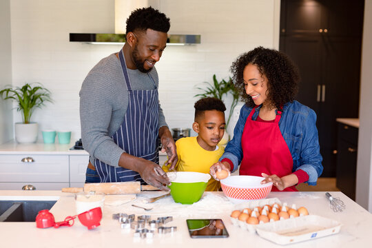 Happy african american parent and son baking together in kitchen