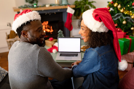 Happy african american couple wearing santa hats, using laptop with copy space on screen