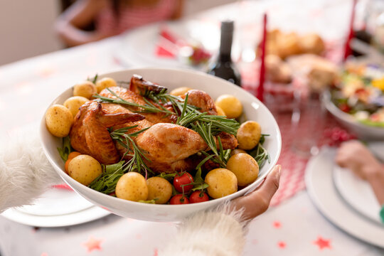 Hand of african american woman holding bowl with chicken and potatoes dish