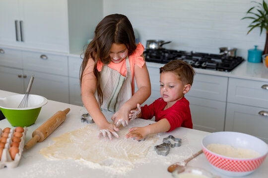 Focused caucasian siblings baking together, making cookies in kitchen