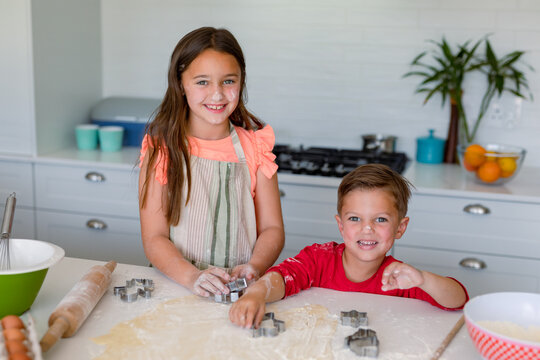 Happy caucasian siblings baking together, making cookies in kitchen