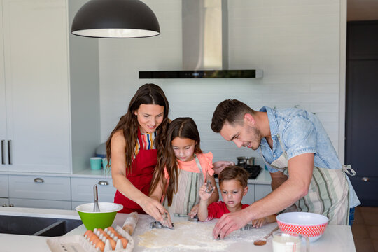 Happy caucasian family baking together, making cookies in kitchen