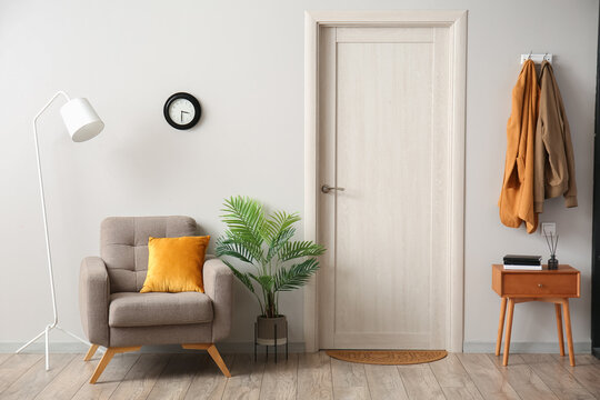 Interior of hallway with armchair, table and door mat