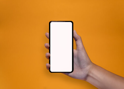Hands holding a smartphone on yellow background