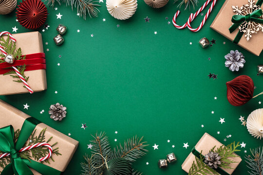 Christmas frame with gift boxes, holaday decorations and confetti on green background.