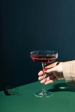 Woman hand holding red champagne in retro glass wine.