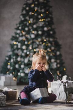Little girl plays christmas toys under christmas tree