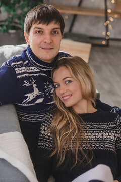 Couple in traditional christmas sweaters posing at home on the sofa