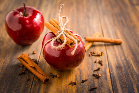 Organic red apples with cinnamon stick and cloves as baking ingredients
