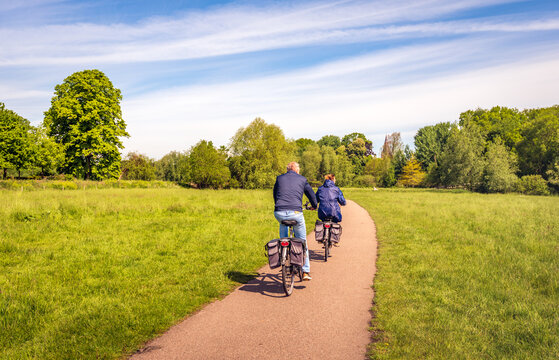 A man and a woman are cycling on a curved bicycle path in a Dutch nature reserve. It is a sunny day in the spring season.