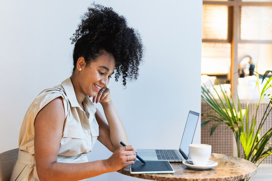 Smiling black woman working on graphic tablet in cafe
