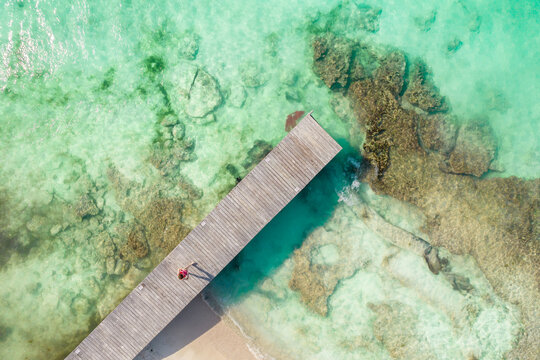 Aerial top view of wooden pier at sunny summer day in Cancun, Mexico, top view. Summertime in Caribbean